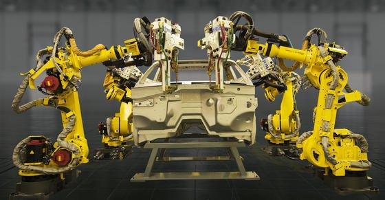 Roboterarme von Fanuc arbeiten an einer Autokarosserie. Künstliche Intelligenz soll sie selbstständig lernen und im Team arbeiten lassen.