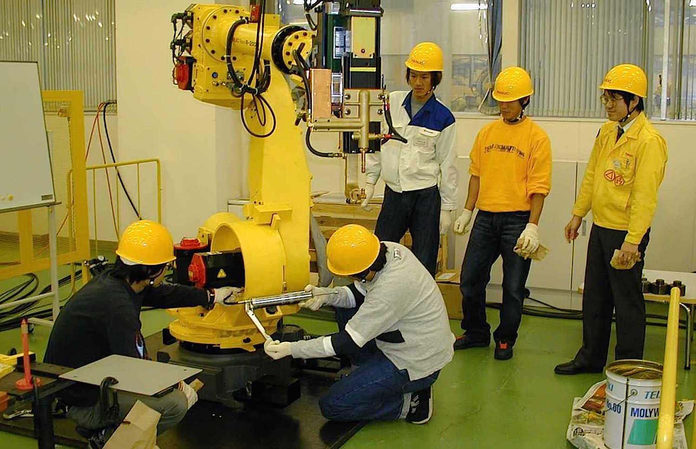 Ingenieure des japanischen Unternehmens Fanuc bauen einen Roboterarm zusammen. Die Technik Deep Learning soll Roboter zu selbstständigem Lernen befähigen.