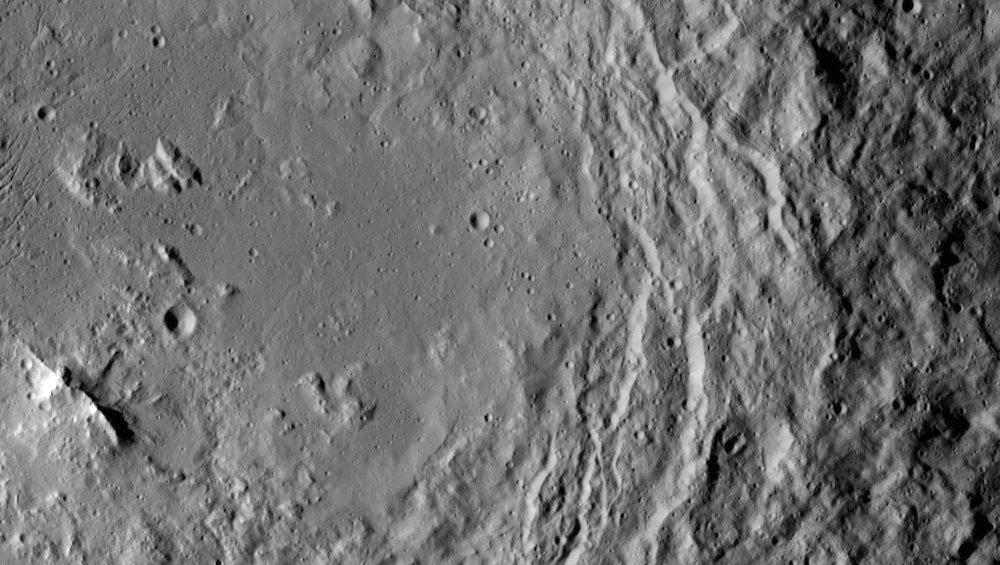 Das Foto zeigt das Innere des Urvara-Kraters. In der linken, unteren Bildecke ist eine Gebirgskette zu erkennen. In der rechten Bildhälfte sind Rutschungen am instabilen Kraterrand in Richtung des Kraterinneren zu sehen.