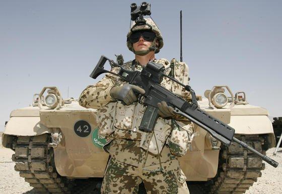 Ein Bundeswehrsoldat der schnellen Eingreiftruppe 2008 im afghanischen Feldlager Marmal bei Masar-i-Scharif mit einem Sturmgewehr G36 vor einem Schützenpanzer Marder 1 A5 M. Weil das Gewehr bei Hitze nicht genau genug schießt, wird es ausgemustert.