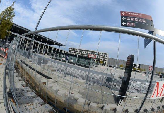 Vor dem Hauptterminal des unfertigen Hauptstadtflughafens BER gehen die Bauarbeiten weiter, während das Terminal selbst wegen Einsturzgefahr gesperrt ist. Jetzt bringen Politiker entnervt einen Abriss des Neubaus ins Gespräch.