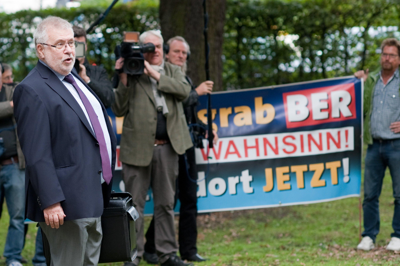 Der Brandenburger Flughafenkoordinator, Staatssekretär Rainer Bretschneider, am 25. September 2015 vor der Aufsichtsratssitzung der Flughafengesellschaft Berlin-Brandenburg: Demonstranten protestieren gegen das Milliardengrab BER. Jetzt rätseln auch Politiker, ob es noch Sinn macht, den Flughafen noch zu vollenden.