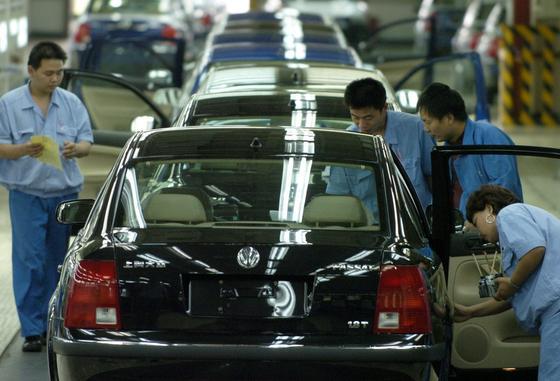 """Chinesische Volkswagen-Mitarbeiter arbeiten im Werk des chinesischen Joint-Venture Partners """"Shanghai Automotive Industry"""" in der Endkontrolle an einem Passat: Jetzt muss VW rund 2000 Fahrzeuge auch in China zurück rufen."""