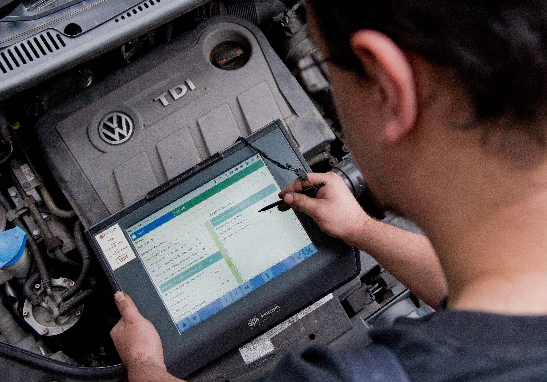 Ein KFZ-Servicetechniker steht mit einem Auslesegerät vor einem vom Abgas-Skandal betroffenen 2.0l TDI Dieselmotor vom Typ EA189 in einem VW Touran.