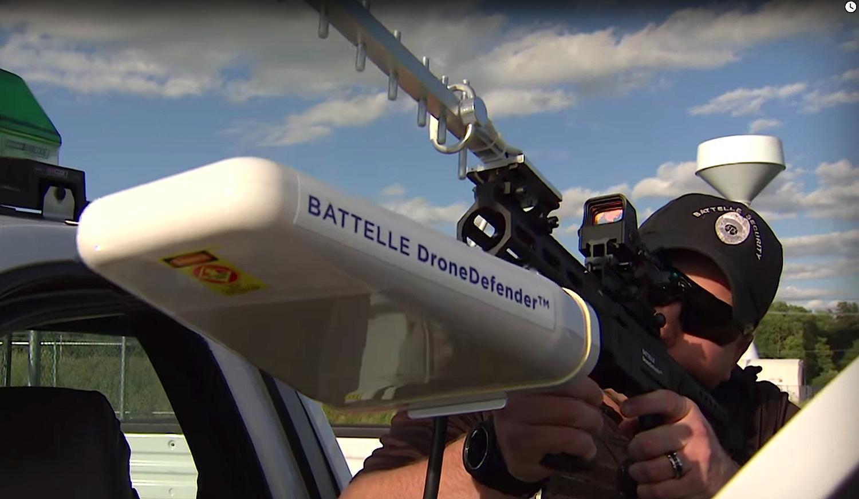 Sicherheitsangestellter zielt mit dem DroneDefender: Das System hat eine Reichweite von 400 m. Battelle will die ersten Geräte Anfang nächsten Jahres an Behörden ausliefern.