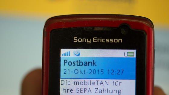 Ein Kunde der Postbank liest am 21.10.2015 in Düsseldorf auf seinem Handy eine mobile Tan ab. Mobilfunk-Kunden der Deutschen Telekom sind Opfer einer Betrugsserie beim Online-Banking geworden. Betroffen sind Kunden verschiedener Banken, die sich die Transaktionsnummern für Bankgeschäfte per SMS auf ihr Handy mit Telekom-Vertrag haben schicken lassen. Der Schaden wird auf mehr als eine Million Euro geschätzt.