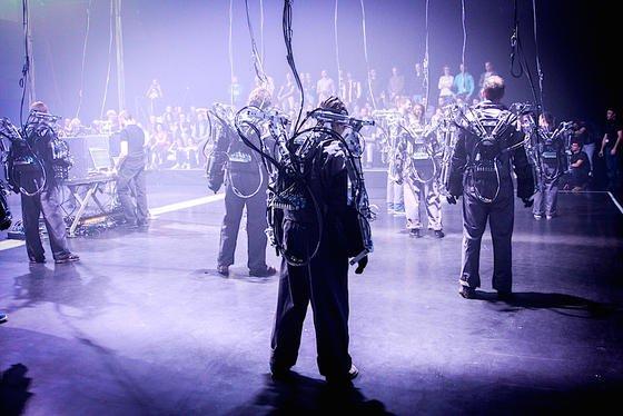 """Unsere neue Realität ist auch von Robotern geprägt. Zur Ausstellungseröffnung wird die Roboterperformance """"Inferno"""" von Louis-Philippe Demers und Bill Vorn gezeigt. Die Besucher schlüpfen dabei selbst in Roboterhüllen, haben aber keine Kontrolle mehr über ihre Exo-Skelette."""