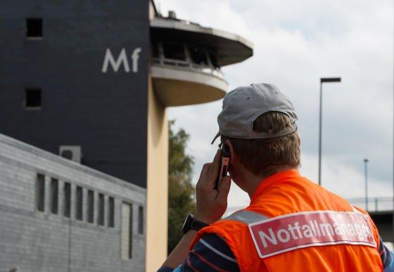Da war es schon zu spät: Ein Notfallmanager der Deutschen Bahn telefoniert am 6. Oktober 2015 in der Nähe des durch ein Feuer zerstörten Stellwerks in Mülheim an der Ruhr. Ursache war ein Kabelbrand.