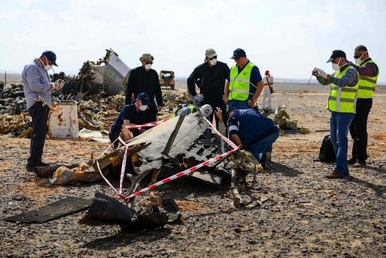 Russische Sicherheitskräfte an einem Wrackteil der abgestürzten Passagiermaschine A321auf der Sinai-Halbinsel: Der britische Geheimdienst kam den Bombenlegern durch abgehörte Telefonate und E-Mails rasch auf die Spur.