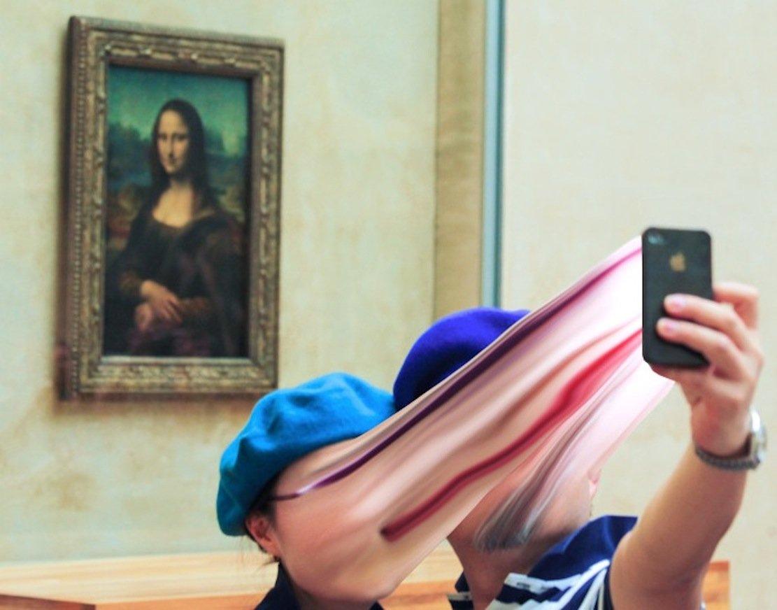 """Zwei Touristen vor dem Bild der Mona Lisa im Louvre von Paris:""""Ich konnte richtig sehen, wie die Gesichter der Menschen mit den Bildschirmen verschmolzen sind, als ob ihre Identität verloren gegangen ist in einem nicht-existenten technologischen Raum."""" FotografAntoine Geiger zu seinen Smartphone-Bildern."""