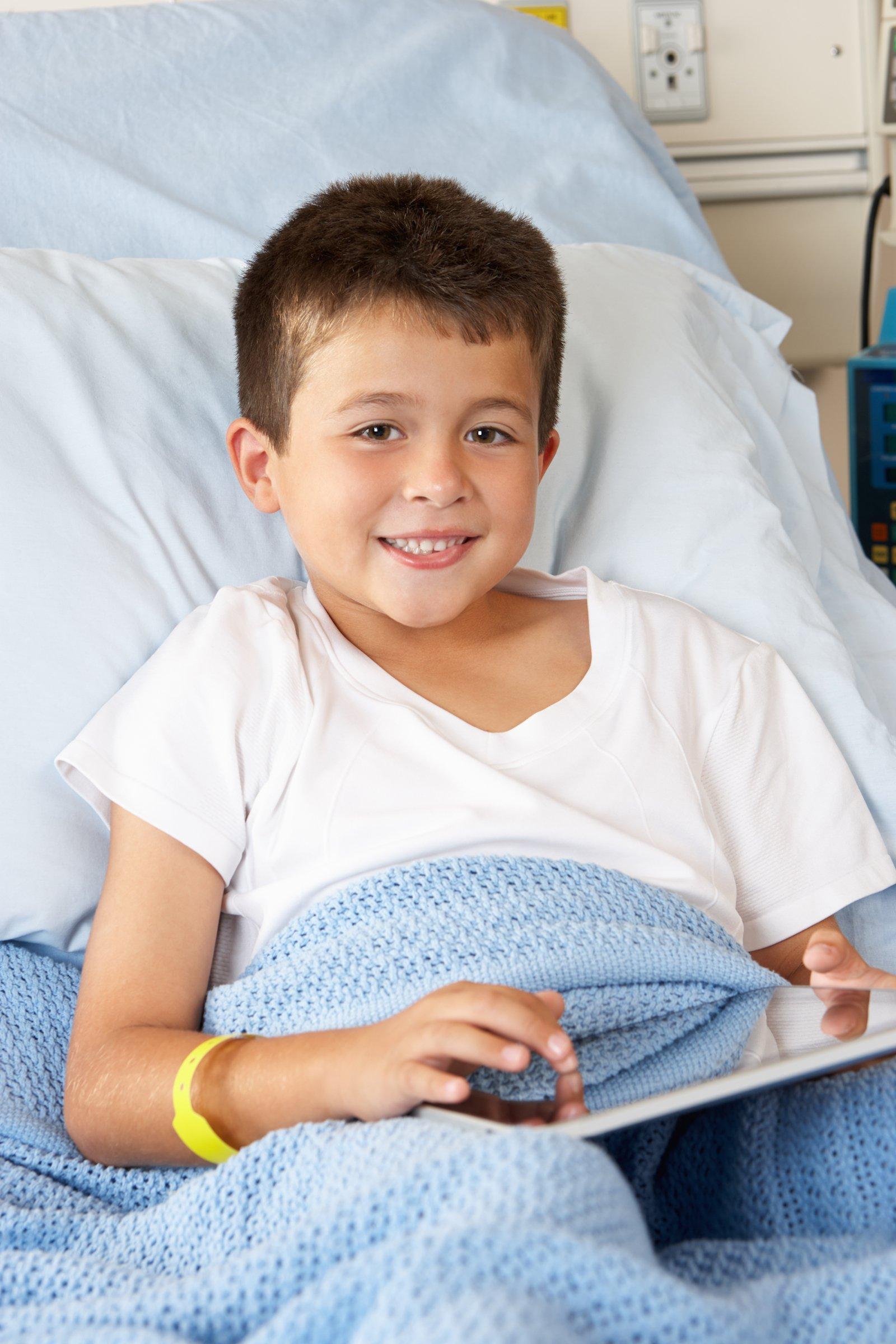 Das kranke Kind verfolgt im Krankenhausbett mit einem Tablet, was Roboter Nao im Klassenzimmer sieht und hört.