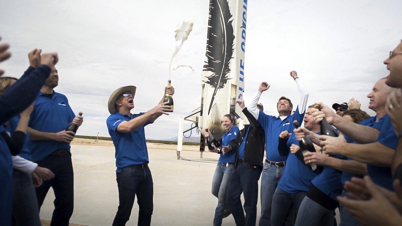 Amazon-Gründer Jeff Bezos – mit Hut und Champagner-Flasche – lässt nach der gelungenen Landung die Korken knallen. Sein Konkurrent Elon Musk beißt sich an diesem komplizierten Landemanöver bislang die Zähne aus.