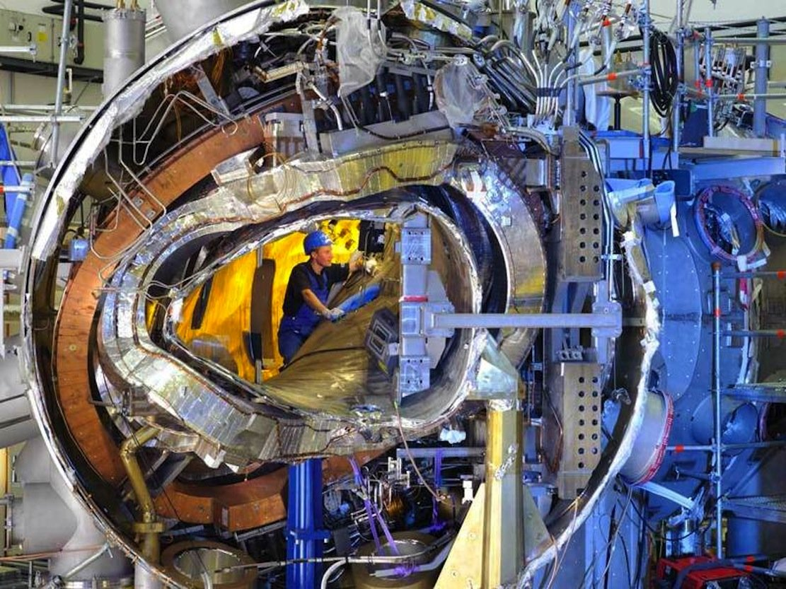 Im November 2011 ließ sich in das Innere des Fusionsreaktors Wendelstein 7-X noch hineinsehen. Von innen nach außen sieht man das Plasmagefäß, eine der verwundenen Stellaratorspulen, eine ebene Spule, die Stützstruktur und das Außengefäß zusammen mit zahlreichen Kühlleitungen und Stromzuführungen.