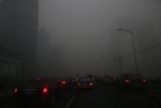 Dicke Luft zur Rush-hour in Peking: Der Staub ist so dicht, dass man kaum noch etwas sehen kann.