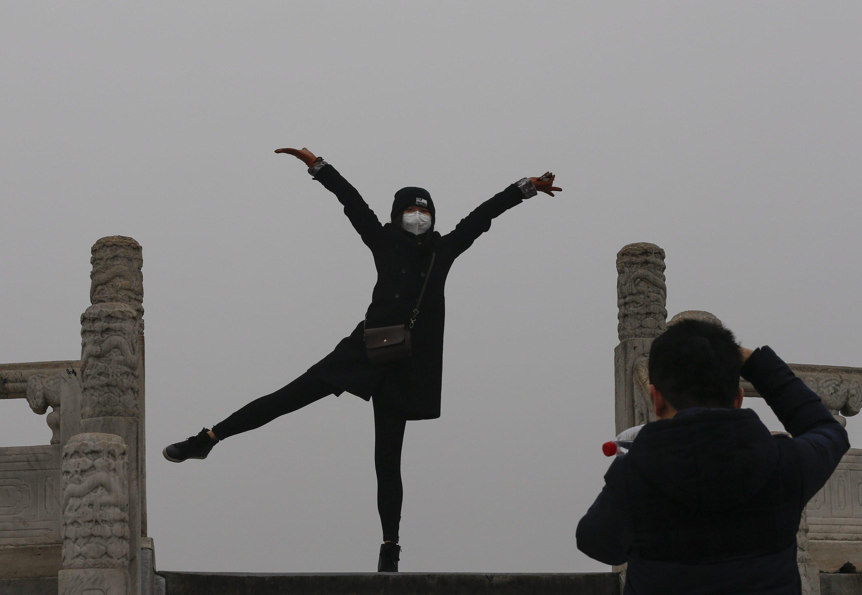 Frau mit Atemmaske vor dem Himmelstempel: Eigentlich kann man den Tempel sehen. Doch der Smog in Peking ist so dicht, dass man selbst Gebäude kaum noch erkennen kann.