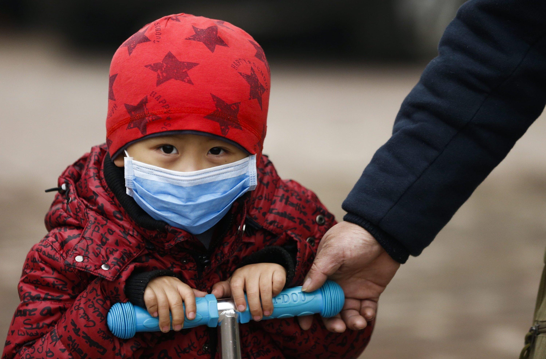 Kind mit Atemmaske in Peking:Wegen der enormen Luftverschmutzung sind Schulen und Kindergärten in Peking geschlossen.