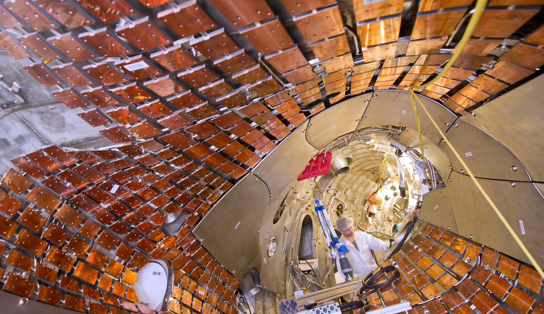 Ein Monteur arbeitet im ringförmigen Plasmagefäß des Forschungsreaktors Wendelstein 7-X.