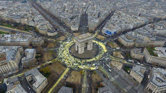 Greenpeace hatte am Freitag den Kreisverkehr am Arc de Triomphe gelb eingefärbt und damit die Sonne symbolisiert als Mahnung für die UN-Klimakonferenz. Mit Erfolg: Die Staaten einigen sich darauf, die Klimaerwärmung auf 1,5 °C zu begrenzen.