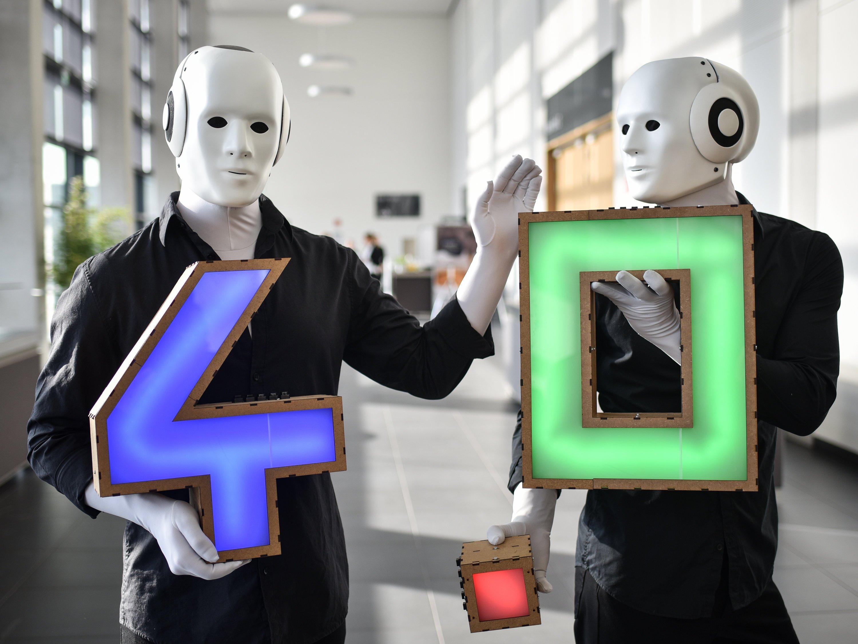Nicht echt: Bei diesen Robotern handelt es sich um verkleidete Menschen. Ein Werbegag zum Start der Plattform Industrie 4.0 im April 2015. Künstliche Intelligenz könnte zum Problem für den Menschen werden. OpenAI will das verhindern.