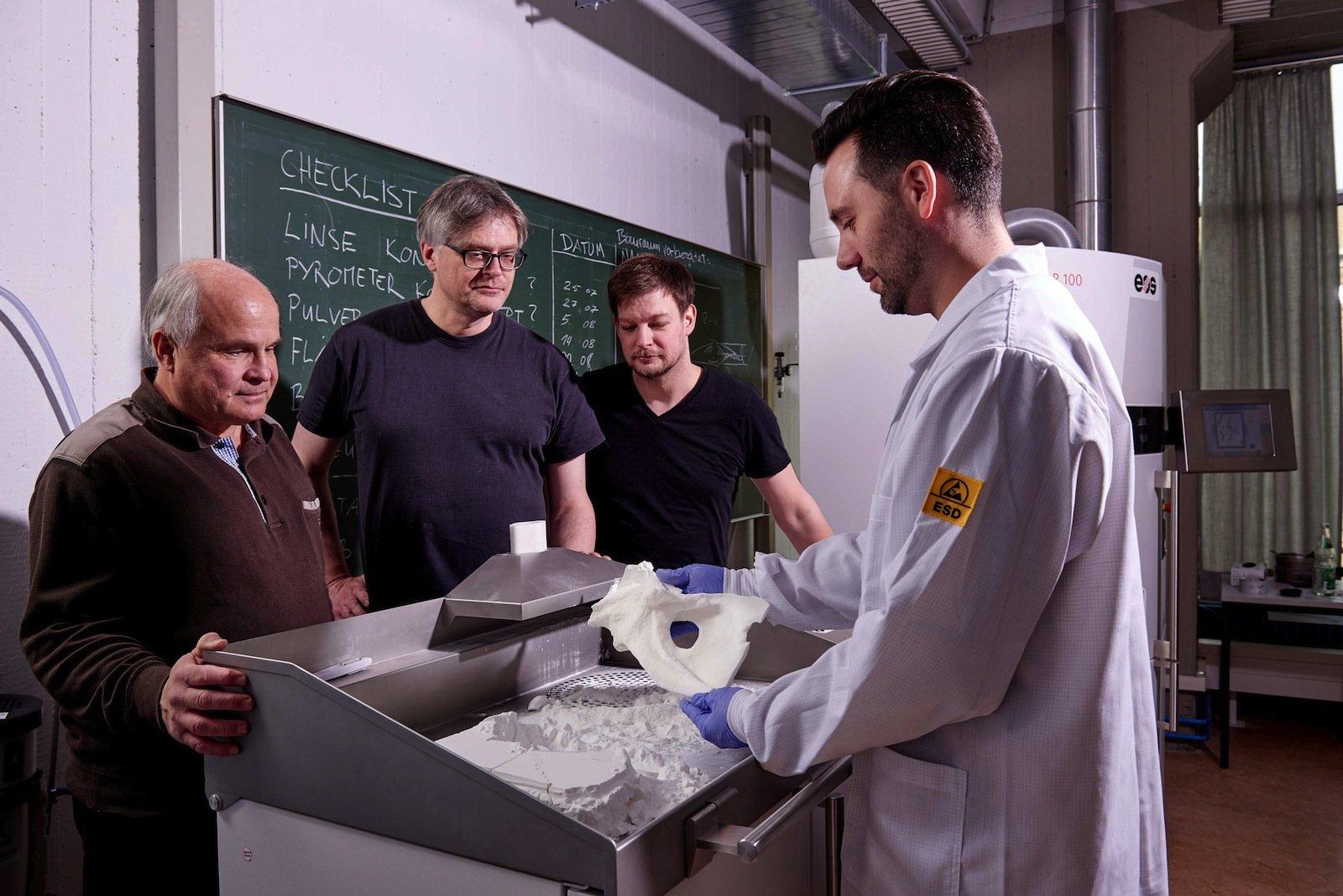 Große Spannung an einem der 3D-Drucker des TU-3D-Labors: Harmut Schwandt, Joachim Weinhold, Ben Jastram und Samuel Jerichow (v. l.) prüfen einen T-Rex-Schädelknochen.