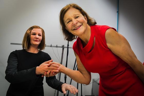 Professor Nadia Thalmann (re.) schüttelt Nadine die Hand. Anders als bisherige Roboter verfügt Nadine über eine eigene Persönlichkeit. Fluch oder Segen?