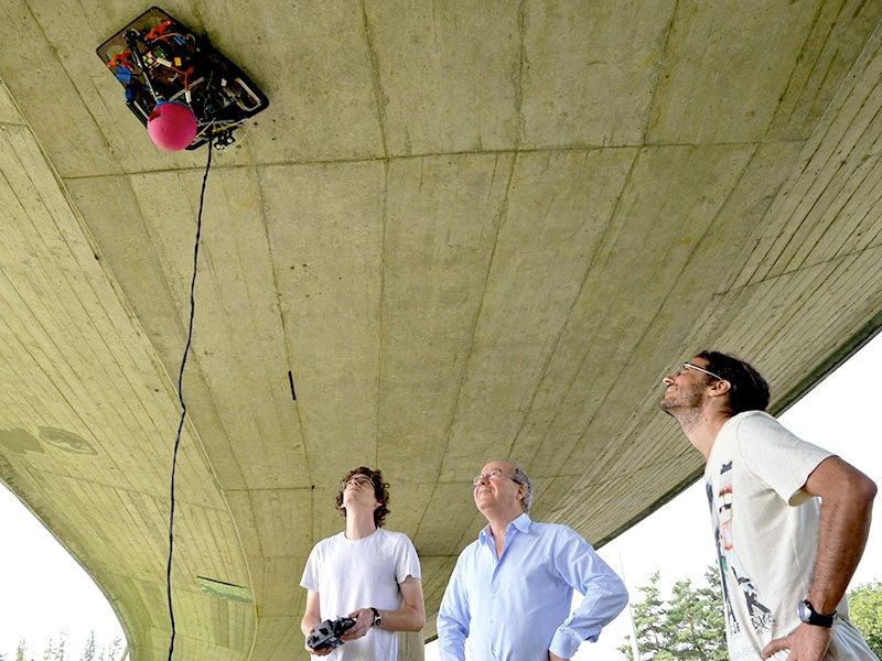 Mit einem Propeller erzeugt C2D2 einen Unterdruck: Der Roboter kann an Brückenunterseiten entlang fahren und mit einem Sensor selbst unsichtbare Materialschwächen aufspüren.