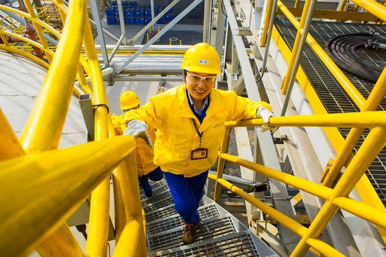 Ingenieurin gut gelaunt bei der Arbeit in einer chemischen Anlage der BASF: Ein angenehmes Betriebsklima ist die beste Voraussetzung für erfolgreiches Arbeiten auch in technischen Bereichen.