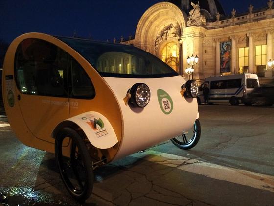 """Das spanische Start-upEvovelo hat sein Dreirad """"mö"""" in Paris vorgestellt. In dem Gefährt können zwei Personen fahren. Angetrieben wird das Velomobil mit Pedalkraft und von einem Elektromotor. Den Strom liefern Solarzellen auf dem Dach."""