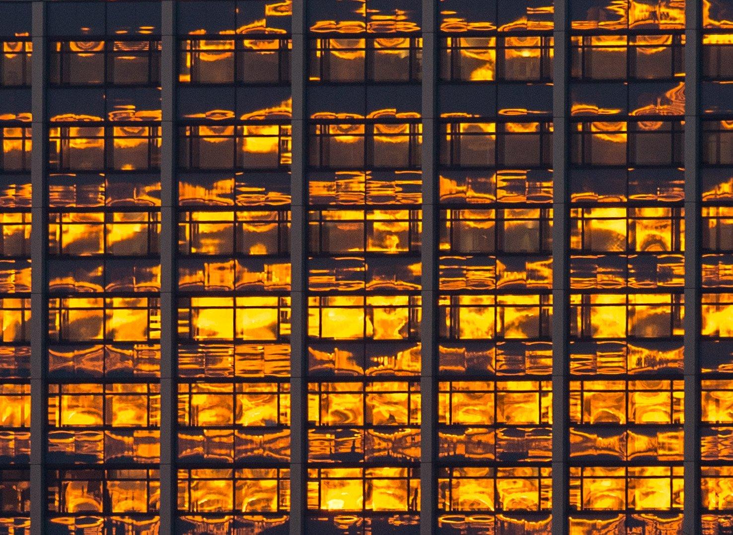 Die Morgensonne spiegelt sich in Hamburg in einer Glasfassade: Wäre auf den Fenstern schon die neue transparente Solarzelle der Leipziger Forscher aufgedampft, würde ultraviolettes Licht eingefangen und zur Stromproduktion genutzt.