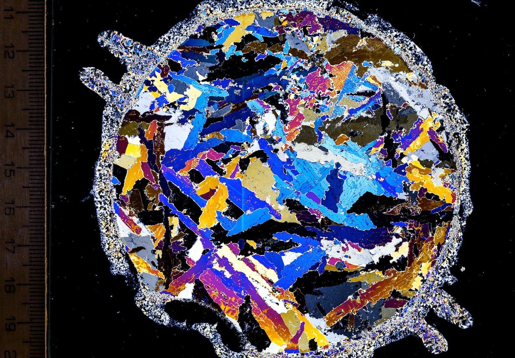 Eingefrorenes Plättcheis: Aufnahme eines Meereis-Bohrkerns (Dünnschnitt) zwischen gekreuzten Polarisationsfiltern. Diese Technik lässt die im Meereis eingefrorenen Eisplättchen in unterschiedlichen Farben schimmern, sodass sie für die Wissenschaftler gut zu erkennen sind.