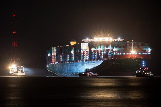 """Mehrere Schlepper haben am 9. Februar 2016 an dem Containerfrachter """"CSCL Indian Ocean"""" der Reederei China Shipping Lines festgemacht und warten auf den günstigsten Zeitpunkt, um den Riesen wieder in das Fahrwasser der Elbe vor Grünendeich bei Stade (Niedersachsen) zu ziehen. Das 400 Meter lange und 59 Meter breite Schiff war bereits am 3. Februar nach einem Schaden an der Ruderanlage aus der Fahrrinne gedriftet und auf Grund gelaufen."""