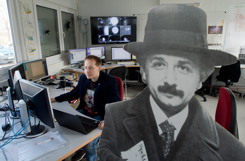 Wissenschaftler Holger Wittel sitzt am 11. Februar 2016 in einem Kontrollraum des Gravitationswellendetektors GEO600 in Ruthe in der Region Hannover neben einem Pappaufsteller, der Albert Einstein darstellt. Im Forschungsprojekt GEO600 sind entscheidende technische Komponenten entwickelt und erprobt werden, die im Gravitationswellen-Observatorium