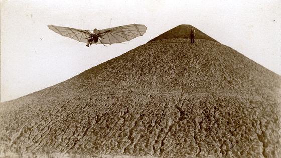 Das Bild zeigt Otto Lilienthal beim Flug vom Fliegeberg in Berlin, den er eigens aufschütten ließ und der somit einer der ersten künstlichen Flugplätze ist. Gemacht hat die Aufnahme der Pionier der Fototechnik Ottomar Anschütz.