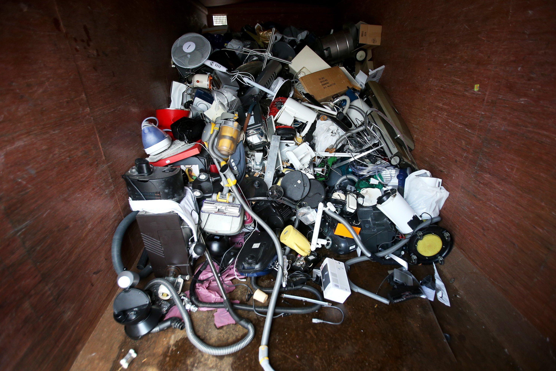 Ausrangierte Haushaltsgeräte und andere Elektrogeräte in einem Sammelcontainer für Elektroschrott:Die meisten Elektrogeräte werden ausgetauscht, obwohl sie noch funktionieren. Das bedeutet: Die Hersteller haben es gar nicht nötig, in ihre Geräte böswillig Mängel einzubauen.