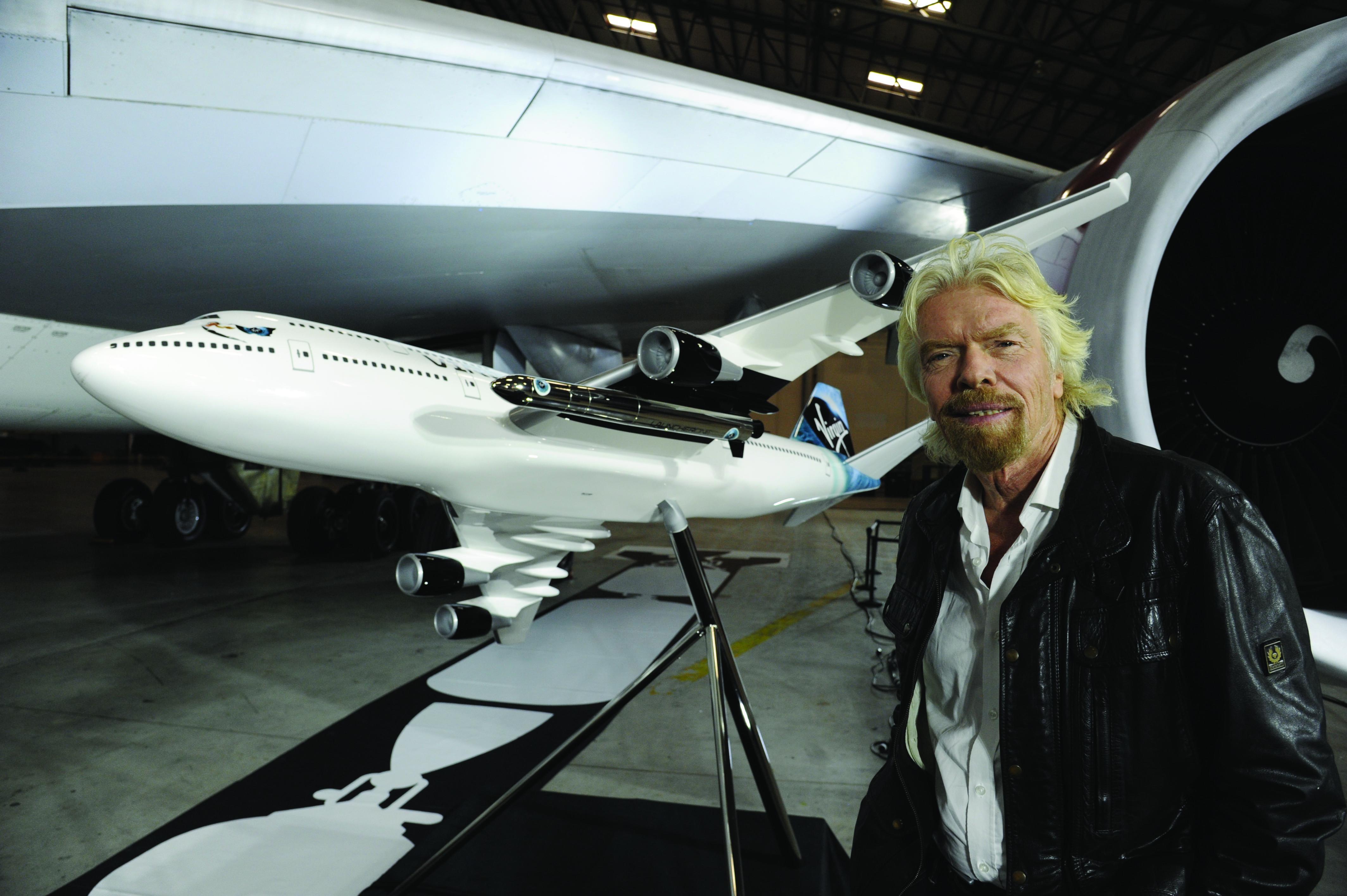 Unternehmensgründer Richard Branson vor einem Modell des Jumbo 747, unter dessen linker Tragfläche die Trägerrakete mit einem Satelliten zu erkennen ist. Die Testflüge sollen 2017 beginnen.