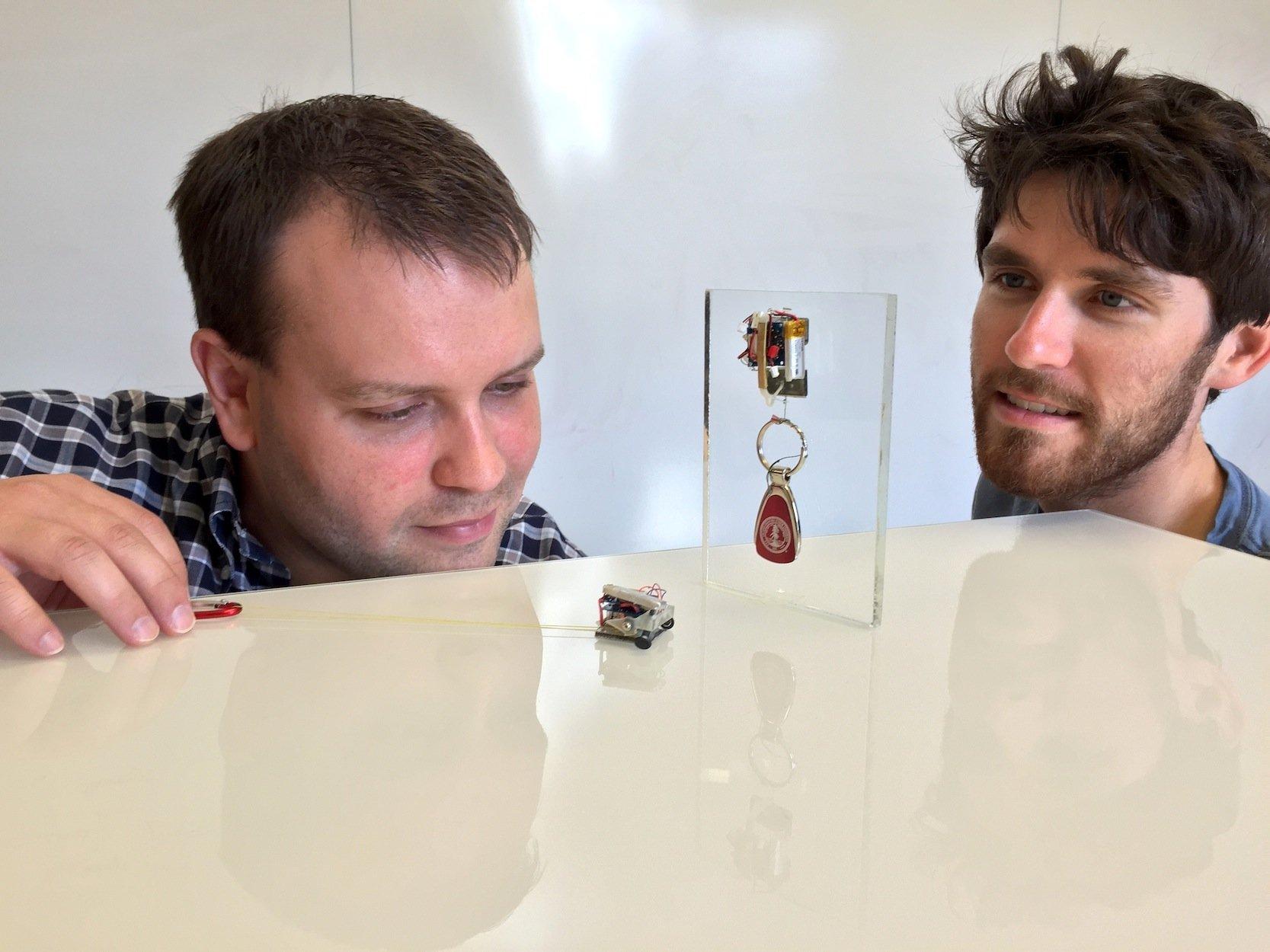 David Christensen (l.) und Kollege Elliot Hawkes von der Standford Universität beobachten, wie ein Mikroroboter samt Schlüsselanhänger einen Wand hochklettert.