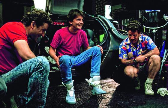 """Am Rande der Dreharbeiten zum Film """"Zurück in die Zukunft 2"""" probiert Hauptdarsteller Michael J. Fox (m.) die selbstschnürenden Schuhe von Nike aus. Jetzt, 30 Jahre später, kommen die Schuhe wirklich auf den Markt."""