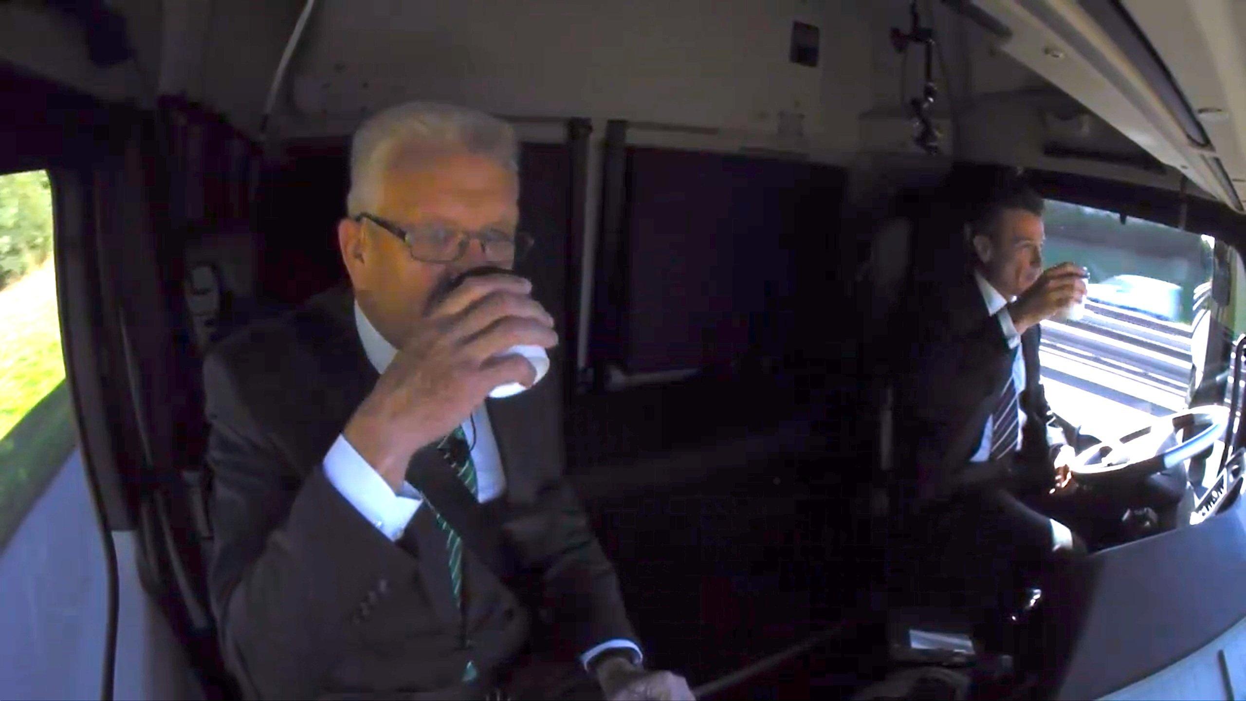Daimler-Truck-Chef Wolfgang Bernhard und Ministerpräsident Winfried Kretschmann beim Kaffeetrinken, während der Actros selbstständig über die A8 steuert.