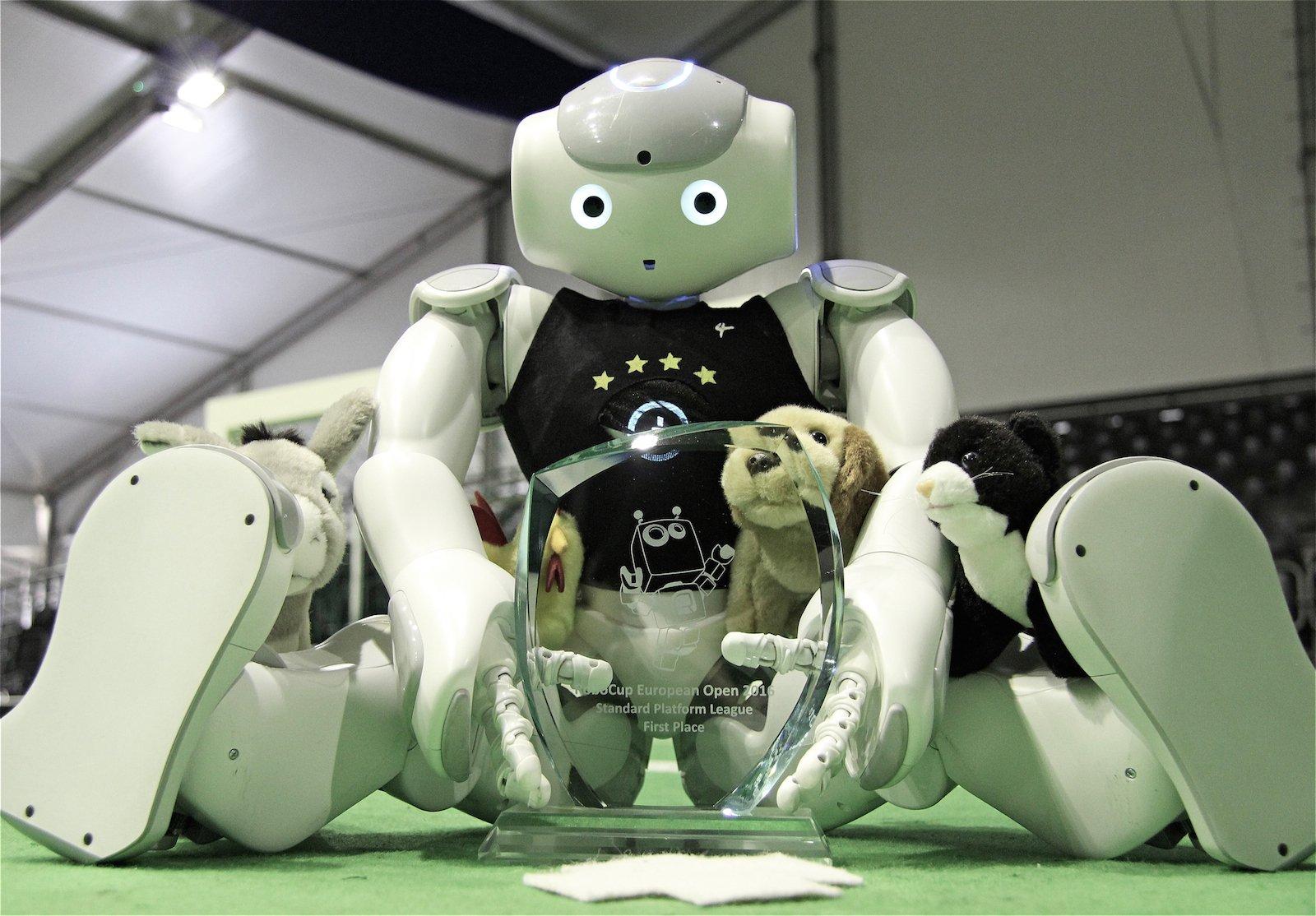 NAO-Roboter des Teams B-Human mit Sieger-Pokal.