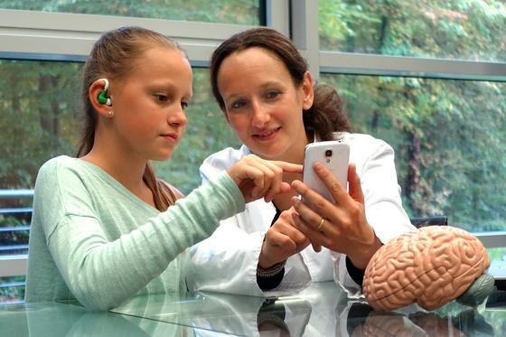 Das Minisensorsystem im Einsatz: Der Messfühler wird im Ohr befestigt und ein Smartphone übermittelt die Daten an einen Rechner, der die Signale auf epileptische Anfälle hin auswertet.