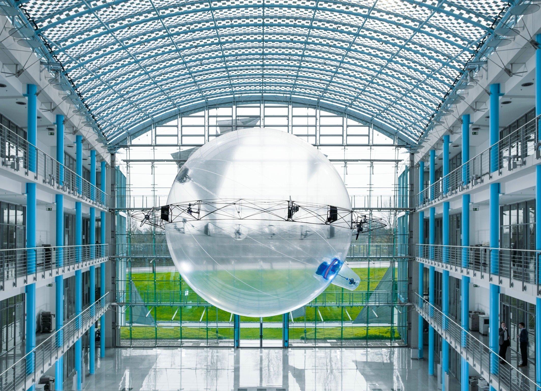 """Das neue Flugobjekt namens """"FreeMotionHandling"""" von Festo besteht aus einem ultraleichten Karbonring mit acht rundum verteilten Mini-Propellern. In der Mitte des Rings sitzt eine drehbare Heliumkugel, an deren Unterseite ein Greifer montiert ist."""