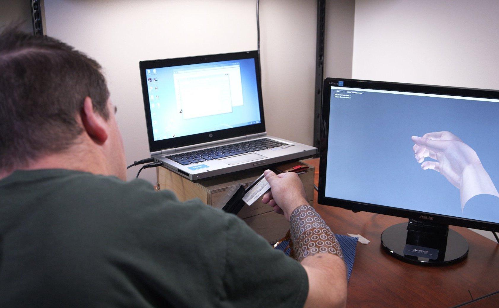 Ian Burkhart, querschnittsgelähmt, kann seine Hände per Gedankensteuerung wieder so bewegen, dass es ihm möglich ist,eine Kreditkarte durch ein Lesegerät zu ziehen.
