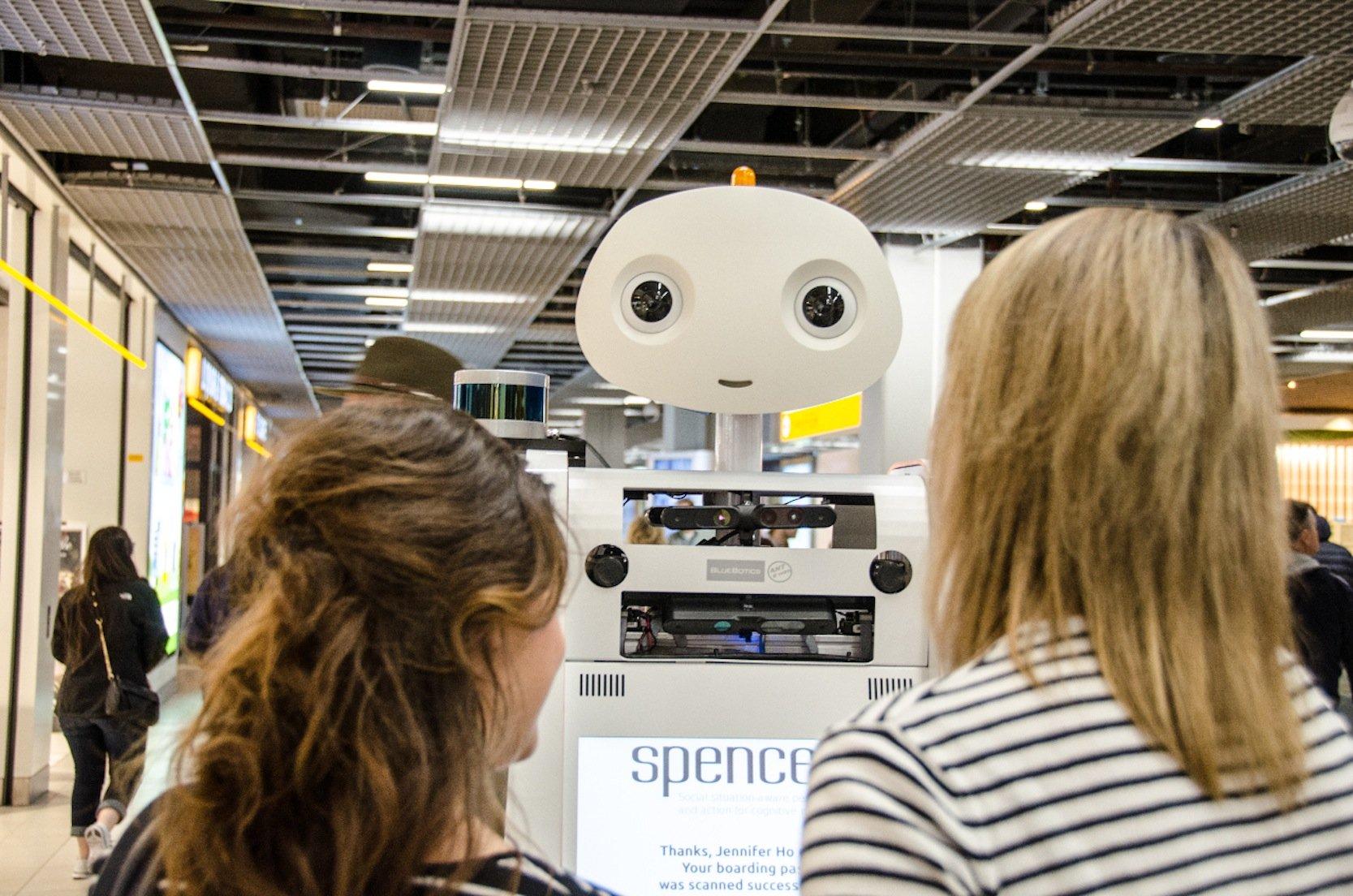 Das schweizerische Unternehmen BlueBotics baute den Roboter für die Fluggesellschaft KLM, die ihn künftig als Lotsen einsetzten möchte. Neben der Universität Twente sind die Albert-Ludwigs-Universität Freiburg, die TU München, die RWTH Aachen, das Centre National de la Recherche Scientifique in Toulouse sowie die schwedische Örebro Universität am Projekt Spencer beteiligt.