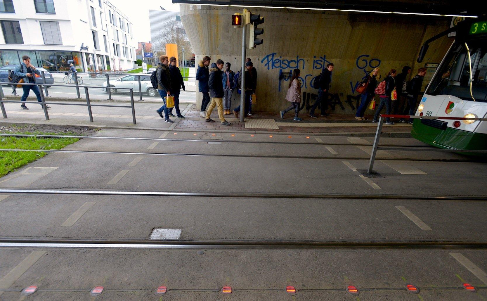 In Augsburg warnen rote LED-Leuchten im Boden abgelenkte Fußgänger, die auf ihr Smartphone starren, vor der Straßenbahn.