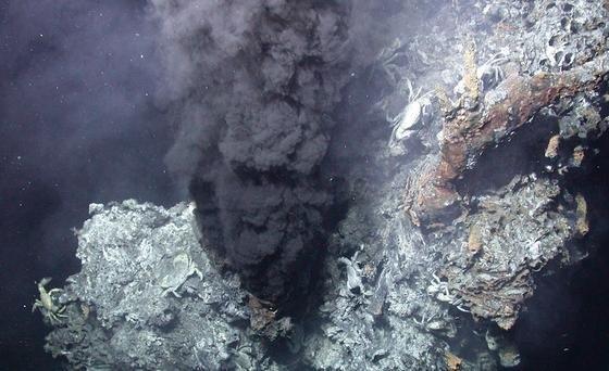 """Schwarzer Raucher:Bei dem """"Rauch"""" handelt es sich um schwarze, staubähnliche Partikel, die im Wasser gelöst sind."""