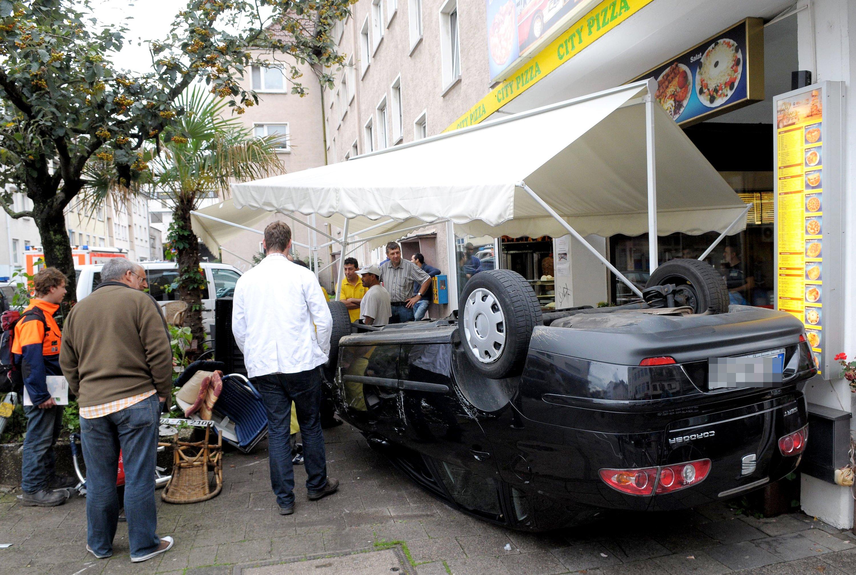 Ein umgekipptes Auto im Zelt einer Pizzeria in Darmstadt: Wie soll sich die Steuerungstechnik autonom fahrender Autos im Fall eines Unfalls mit verschiedenen Handlungsmöglichkeiten entscheiden? Ist der Crash mit einem Auto der Kollision mit Fußgängern vorzuziehen? Damit beschäftigen sich derzeit Forscher in Großbritannien und Deutschland.
