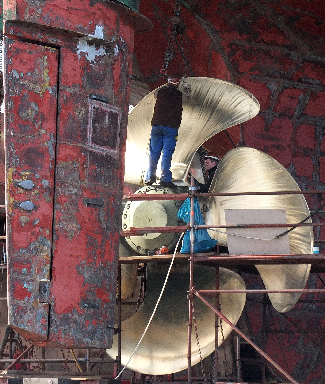 Reinigung eines Schiffsrumpfes und Montage einer neuen Schiffsschraube in einer Werft in Hamburg: Meist enthalten Schiffslacke, die den Rumpf vor Bewuchs schützen sollen, giftige Substanzen, die sich nach und nach im Wasser lösen.