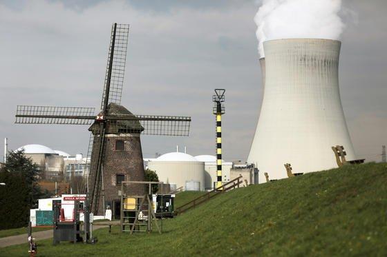 Dampf steigt hinter einer Windmühle bei Antwerpen (Belgien) aus den Kühltürmen des Atomkraftwerks Doel. Während Deutschland 2022 Akw-frei sein will, sehen die Energiepläne der EU-Kommission den Ausbau der Kernkraft vor.