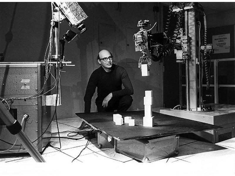 Marvin Minsky mit seinem berühmten Roboterarm Ende der 1960er/Anfang der 1970er Jahre: Dieser Arm verfügte über eine Videokamera und wurde von einem Computer gesteuert. Bei diesem Experiment baut der Minsky-Arm mit Bauklötzen einen Turm.
