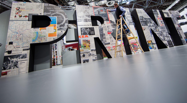 """""""Print"""" steht in überdimensionalen Buchstaben auf einem Messestand der drupa. Dabei heißt der neue Trend in der Druckindustrie """"Print 4.0"""". Dahinter verbirgt sich die digitale Vernetzung von Maschinen und Systemen."""